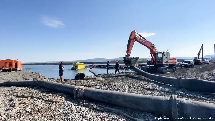 A digger pulls up a pipeline in the tundra