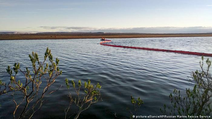 Rescuers work to prevent the spread from an oil spill