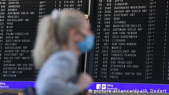 Девушка в маске на фоне табло с расписанием рейсов в аэропрту Франкфурта