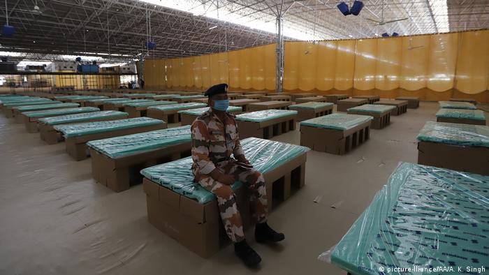 A police officer sits on a disposable bed made out of cardboard at a building that has been converted into a hospital in New Delhi, India
