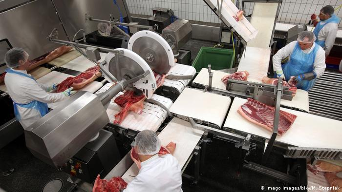 Workers using machines to cut meat at a Tönnies slaughterhouse in Germany