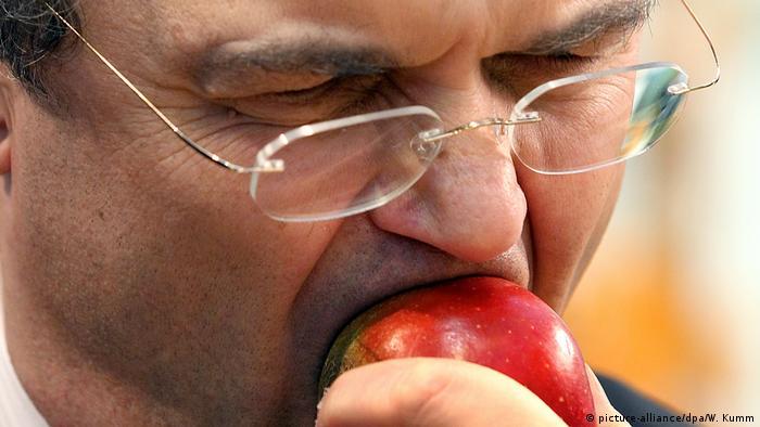 Мужчина кусает яблоко