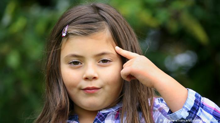Young girl taps with a finger at the side of her head (Copyright: picture-alliance/Blickwinkel/fotototo)