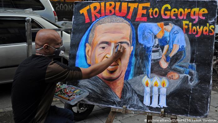 Художник в индийском городе Мумбаи работает на улице над картиной, посвященной памяти Джорджа Флойда