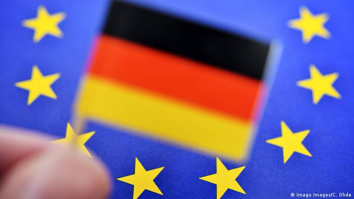German flag in front of an EU flag
