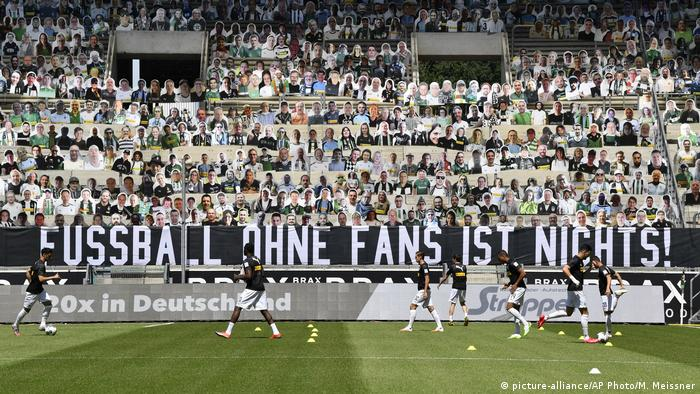 A banner in a stadium reads 'Football is nothing without the fans'