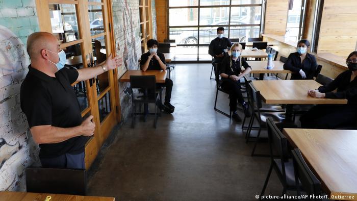 Der Besitzer eines Sushi-Restaurants in Dallas im Bundesstaat Texas erläutert seinen Angestellten Corona-Verhaltensregelnhmen (Foto: picture-alliance/AP Photo/T. Gutierrez)