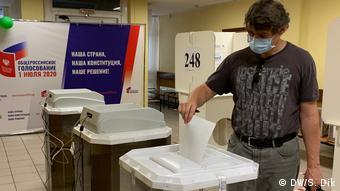 На одном из избирательных участков в Москве мужчина бросает бюллетень в урну
