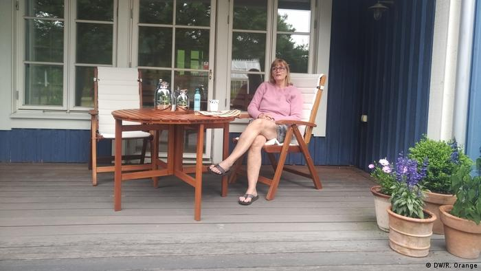Kerstin sitting on the porch of the house she owns in Sweden