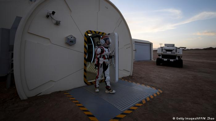 A woman wearing a spacesuit walking out of Mars Base 1, a C-Space Project, in the Gobi Desert