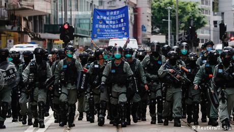 Riot police officers walk as anti-government protesters march during the anniversary of Hong Kong's handover to China from British rule