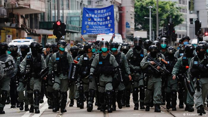 Riot police in Hong Kong walk as anti-government protesters march during a demonstration on July 1, 2019