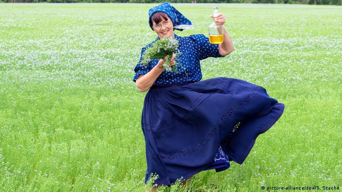 Экскурсовод из Шпревальда Гизела Христл (Gisela Christl) с букетом цветущего льна и льняным маслом