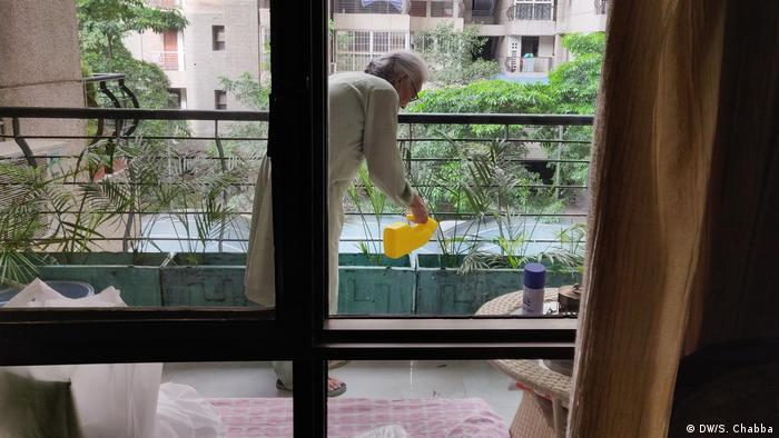 Kaur steps out on her balcony to care for her plants amidst India's COVID-19 restrictions