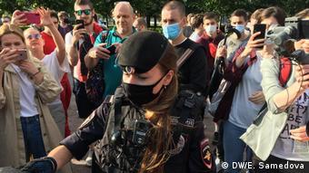 Полицейская раздает маски участникам акции против поправок к конституции на Пушкинской площади в Москве
