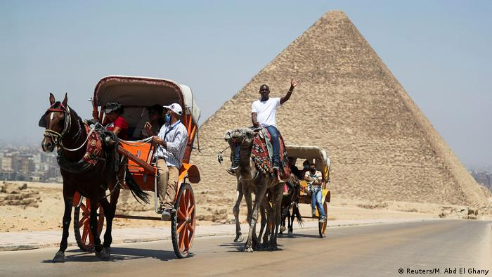 Tourists ride a cart in front of the Great Pyramid of Giza after reopening for tourist visits