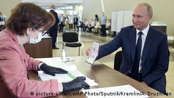 Путин показывает члену избирательной комиссии свой паспорт