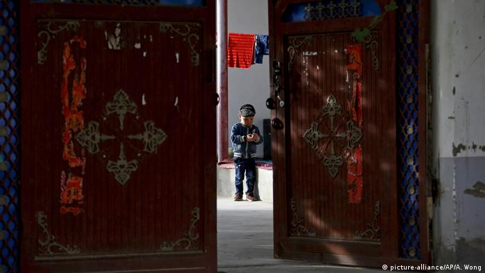 A Uighur child plays alone in the courtyard of a home in China's Xinjiang region