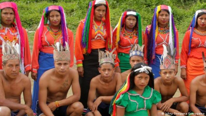 A group of indigenous people from Colombia assemble for a photo. Women stand in coloral garments and head coverings in the bike while men and boys kneel in the front