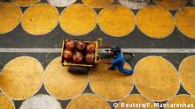 A man pushes a cart filled with liquefied petroleum gas (LPG) cylinders on a street painted with circles for people to maintain social distancing after a few restrictions were relaxed during an extended lockdown to slow the spread of the coronavirus disease (COVID-19) in Mumbai, India, July 1, 2020. REUTERS/Francis Mascarenhas TPX IMAGES OF THE DAY
