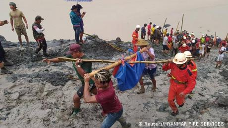 People carry a dead body following a landslide at a mining site in Phakant, Kachin State City, Myanmar July 2, 2020