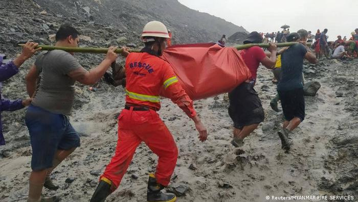 Rescue workers carry a body from the site of a landslide