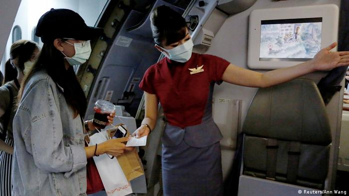A crew member of an Asian airline shows a passengers an available seat during a fake flight organized for people who are not allowed to leave Taiwan due to coronavirus restrictions but are offered the travel experience during a simulated flight.