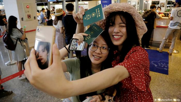 Two women hold their passports and take a selfie