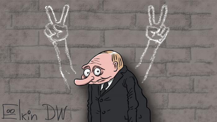 Карикатура - смущенный Владимир Путин перед стеной, на которой нарисованы две руки со знаком победы. Свои руки он спрятал глубоко в карманы пальто.