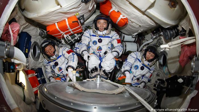 تظهر الصورة ثلاثة رواد فضاء صينيين في تدريب على كبسولة تحاكي عودة سفينة شنتشو 9 الفضائية إلى الأرض.