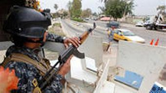 Schwerbewaffneter Polizist am Straßenrand (Foto: AP)