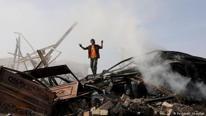 Foto de una persona parada entre escombros en Yemen