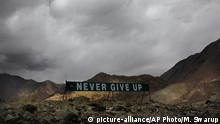 In this Sept. 14, 2017, file photo, a banner erected by the Indian army stands near Pangong Tso lake near the India China border in India's Ladakh area. Modi made an unannounced visit Friday, July 3, 2020, to a military base in remote Ladakh region bordering China where the soldiers of the two countries have been facing off for nearly two months. Modi's visit comes in the backdrop of massive Indian army build-up in Ladakh region following hand-to-hand combat between Indian and Chinese soldiers on June 15 that left 20 Indian soldiers dead and dozens injured, the worst military confrontation in over four decades between the Asian giants. (AP Photo/Manish Swarup, File) |