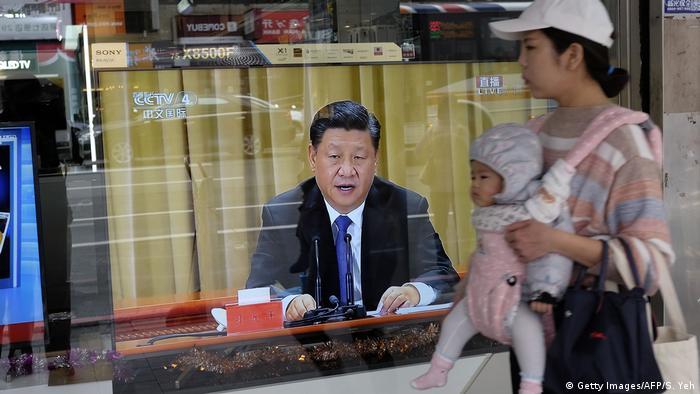 Майка с дете минават край витрина с телевизор, предаващ реч на Си Дзинпин
