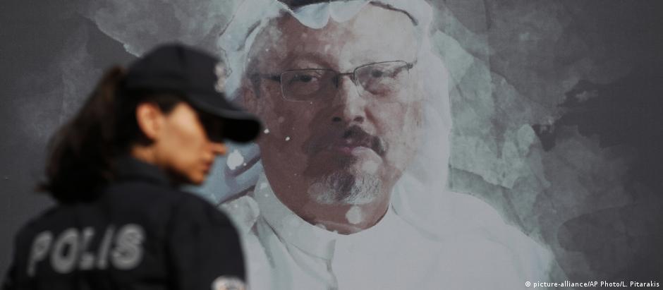 A Turkish police officer walks past a picture of slain Saudi journalist Jamal Khashoggi