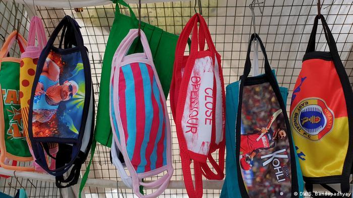 বাঙালির মুখোশেও ফুটবলের দলাদলি। ইস্টবেঙ্গল, মোহনবাগানের জার্সির রঙে মুখোশ। (DW/S. Bandopadhyay)