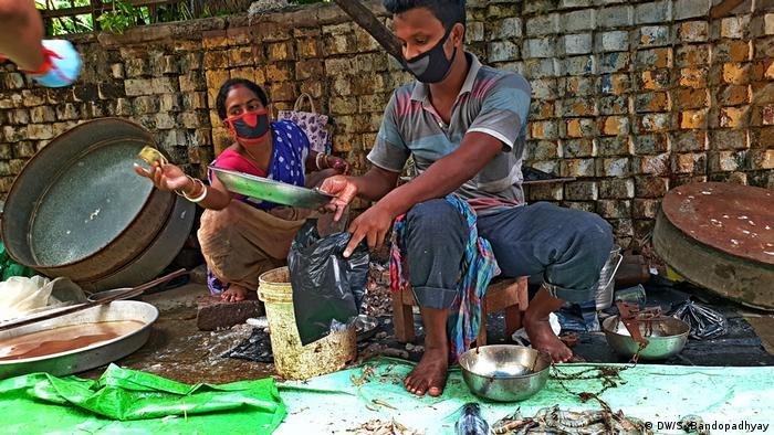 মাছ বিক্রেতা থেকে শুরু করে যে মহিলা মাছ কুটে দেন, সবাই সাবধানী। (DW/S. Bandopadhyay)