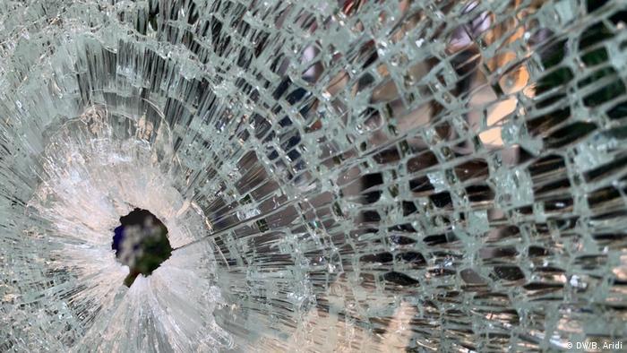 Foto de una ventana de vidrio atravesada por una bala