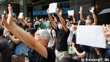 Supporters raise white paper to avoid slogans banned under the national security law as they support arrested anti-law protester outside Eastern court in Hong Kong, China July 3, 2020. REUTERS/Tyrone Siu