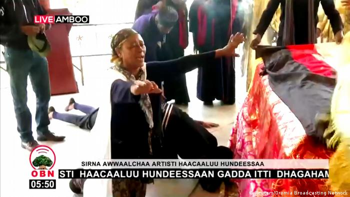 A woman reacts next to the coffin of Ethiopian musician Haacaaluu Hundeessaa during his funeral in Ambo, Ethiopia, July 2, 2020, in this still image from a video