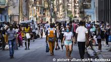Pedestrians wearing protective face masks as a precaution against the spread of the new coronavirus, come into the streets after an easing of COVID-19 related lockdown restrictions, in Havana, Cuba, Friday, July 3, 2020. (AP Photo/Ramon Espinosa)  