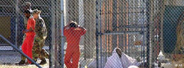 An inmate at Guantanamo is escorted by two guards while other prisoners are seen in cells