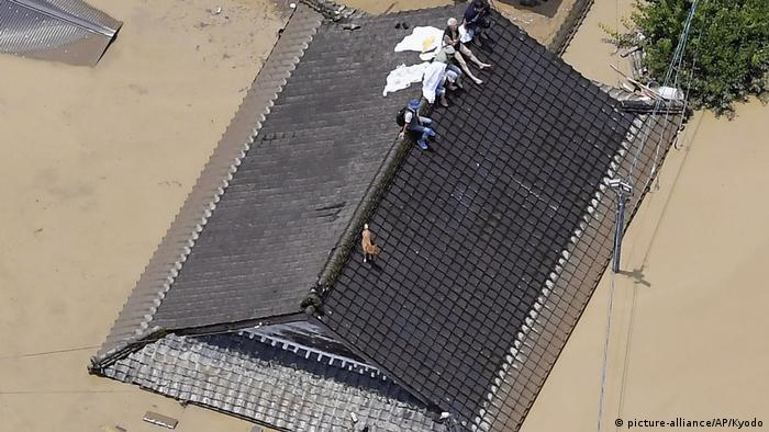 Several people sit on the roof of a flooded building