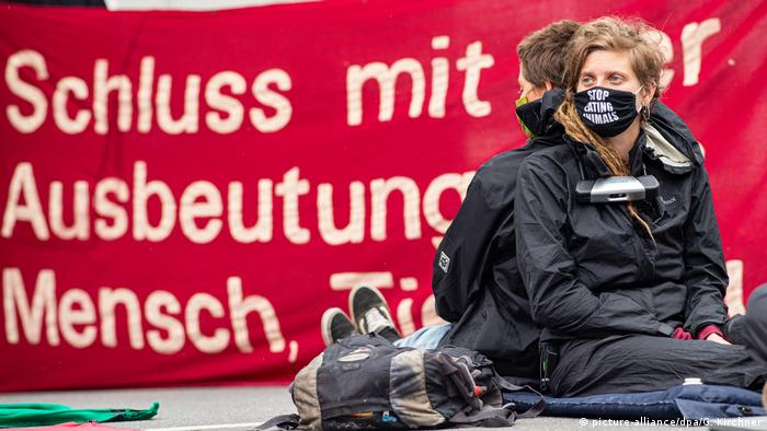 Two demonstrators sitting in front of banner (picture-alliance/dpa/G. Kirchner)
