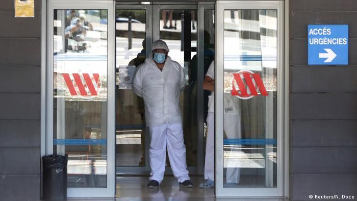 Krankenkausmitarbeiter mit Mundschutz und Schutzkeidung stehen in der offenen Tür eines Krankenhauses in Lleida