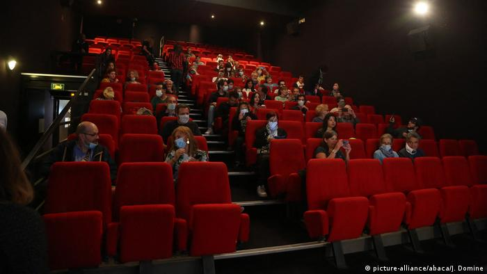 People sit in a reduced capacity theater in Paris