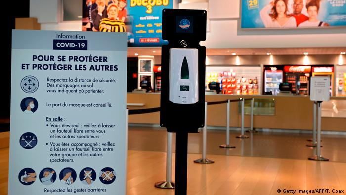 A warning sign and disinfectant at a movie theater in Paris