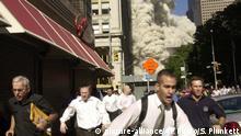 USA New York | Menschen rennen während im Hintergrund einer der Türme des World Trade Centers zusammenbricht