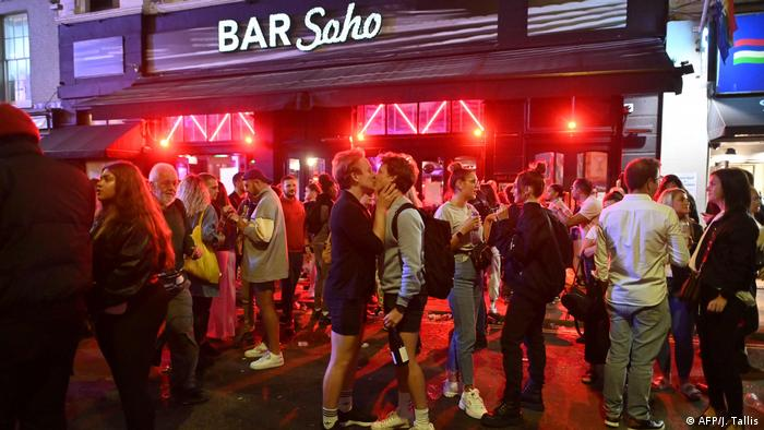 A couple kiss as revellers drink in the street around them outside a bar in the Soho area of London, as restrictions are further eased during the novel coronavirus COVID-19 pandemic