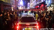 TOPSHOT - A car tries to drive along a street filled with revellers drinking in the Soho area of London on July 4, 2020, after the police re-opened the road at 2300 as restrictions are further eased during the novel coronavirus COVID-19 pandemic. - Pubs in England reopen on Saturday for the first time since late March, bringing cheer to drinkers and the industry but fears of public disorder and fresh coronavirus cases. (Photo by JUSTIN TALLIS / AFP) (Photo by JUSTIN TALLIS/AFP via Getty Images)